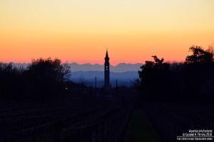 Il campanile di Torrazza Coste e le alpi al tramonto